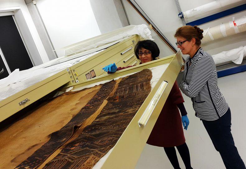 Rangi Te Kanawa and Dr Karyne Rogers viewing a cloak in Te Whare Pora, Te Papa's weaving store.