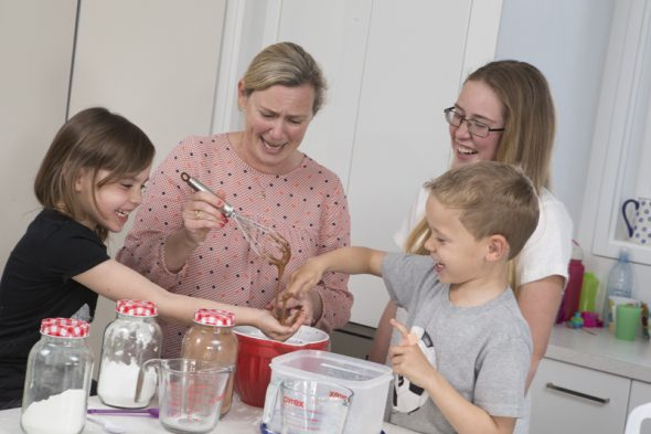 The Gibbon family – Sasha, Melinda, Jessica, and Luca –baking. Luca has a special banana chocolate-chip muffin recipe that he loves to make. Photograph by Norm Heke, Te Papa, 2015