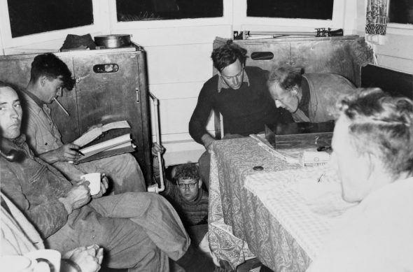 Dick Dell (holding cup) and other members of the 1954 expedition in the cabin of the Alert. Others recognisable from left are Dave Garner, John Yaldwyn (in stairwell), Elliot Dawson, Ray Forster, with Stephen Barker (from Wharekauri, Chatham Island) in right foreground. Image: Te Papa MA_B023471