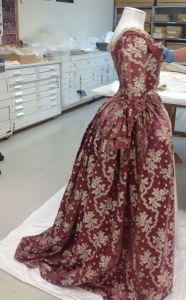 Here we are carrying out the final fitting of both the dress to unsure that the garment is properly supported but not under any stress. At this point we can also adjust the final height of the ensemble and check the silhouette that has been created. Photo by S. Gatley, copyright Te Papa.