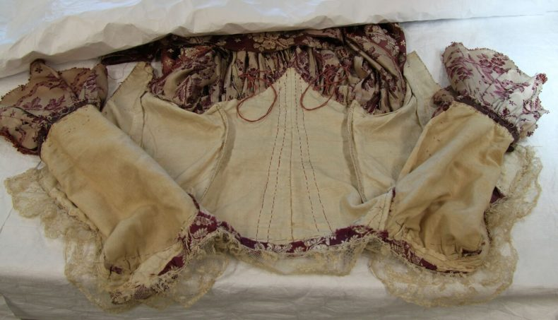 PC000071, robe a l'anglaise retroussee, c 1780. Interior of bodice, showing lace, conical bodice shape and cords that hook onto buttons on the reverse of the gown. Photo by A. Peranteau, copyright Te Papa.