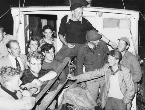 Members of the Chatham Islands 1954 Expedition on the aft deck of MV Alert on their return to Lyttelton, 12 February 1954. John Yaldwyn wearing his spare pair of glasses at lower left. Others approximately left to right are Jock Moreland, John McIntyre (with pipe), Ray Forster, Daphne Marshall, Betty Batham, Dave Garner, Alex Black (seated, captain), Dick Dell, George Knox and Elliot Dawson. Image: Te Papa MA_B.023472