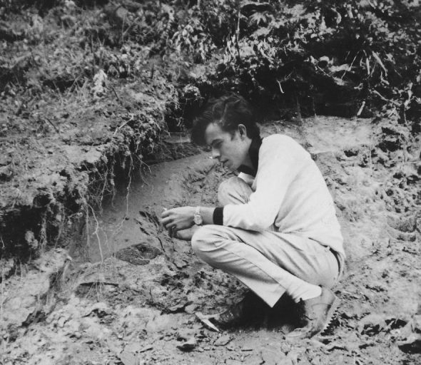 A 19-year-old Bruce Marshall collecting fossil molluscs from the classic roadside fossil locality at Te Piki, between Whangaparaoa and Hicks Bay, in 1967. Image: Graham Spence, courtesy of Bruce Marshall, Te Papa