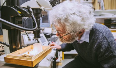 Jean-Claude inspect some specimens under the new macroscope, 2016. Te Papa.