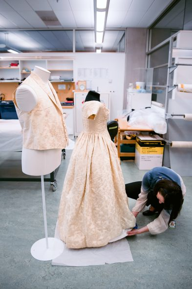 Textile conservator Anne Peranteau prepares William and Sarah Rhodes wedding waistcoat and dress for display. 27 Sept 2016. Te Papa