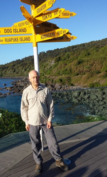Te Araroa hiker at Stirling Point sign, Bluff