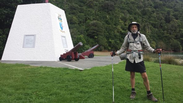 Te Araroa hiker in front of monument at Ship Cove