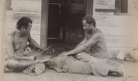 Two Samoan men tattoo a man lying on the floor