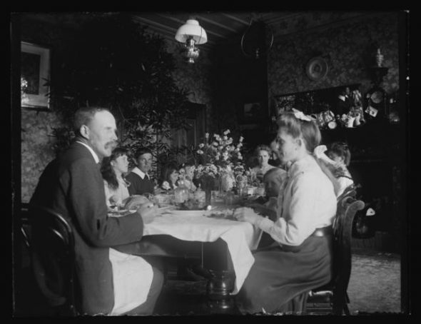 This photograph of the Adkin family dinner, taken in 1905, captures something of the formality of colonial Christmases. It is likely that a hot roast dinner was on the menu, although traditional adornments have been replaced by a vase of fresh flowers. Xmas (Christmas) dinner 25.12.05 , 25 December 1905, Levin, by Leslie Adkin. Gift of G. L. Adkin family estate, 1964. Te Papa (A.005936)