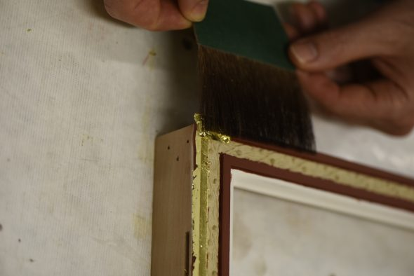 Placing gold onto wet surface, gently pressing down, Photograph by Matthew O'Reilly, Te Papa