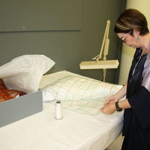 Deborah Crowe consulting on the treatment of her work in the textile conservation lab at Te Papa.