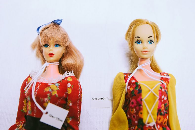 Two 70s Barbies wearing 70s outfits. Their faces are a much more yellowy/green colour than their bodies