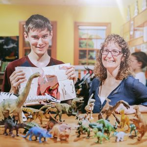 Eric and his mum stand beside some of his dinosaur collection