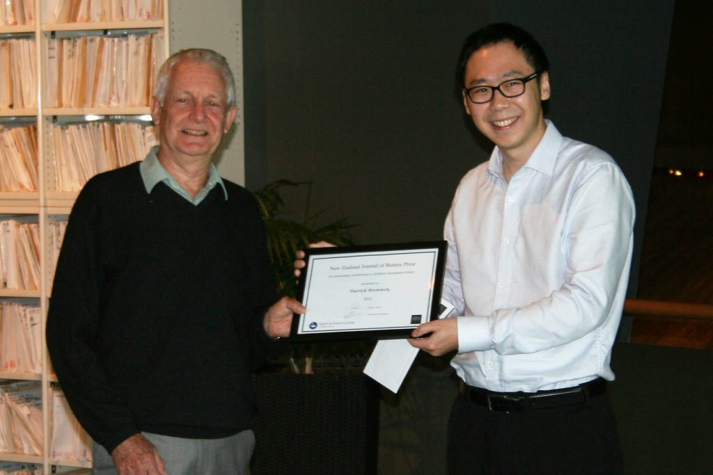 Pat receiving the award from Fei He, Manager of the Publishing Programme, Royal Society of New Zealand.  Photo Antony Kusabs. (c) Te Papa.