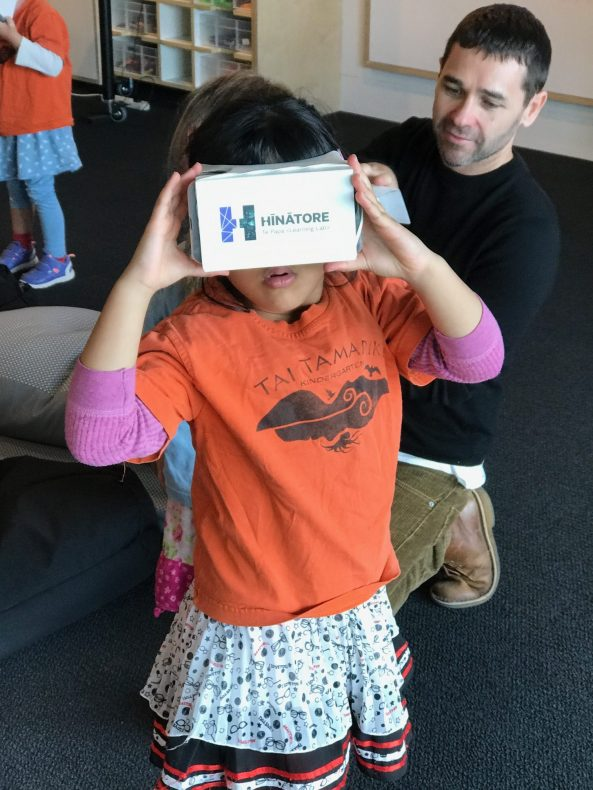 A child uses a Google Cardboard virtual reality headset