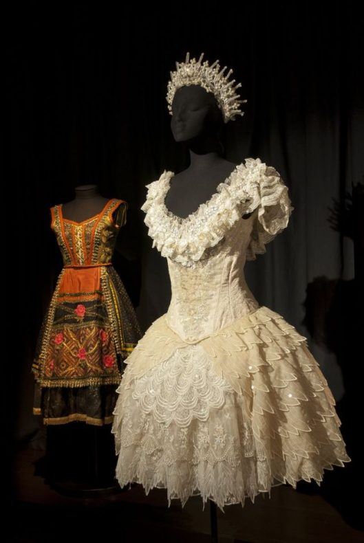 Two costumes, one colourful and featuring a lot of orange, the other cream