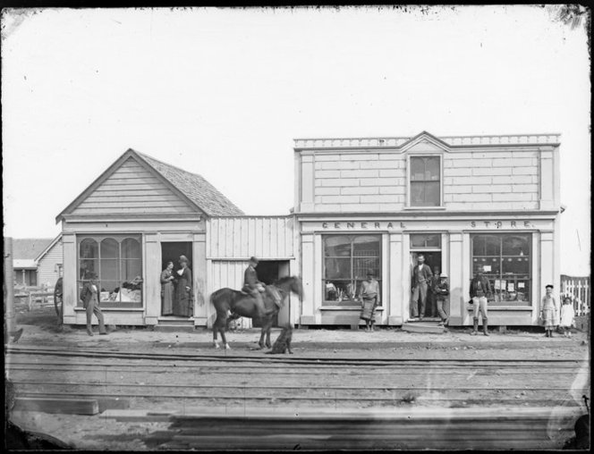 Customers mill around outside the general store, around 1878.