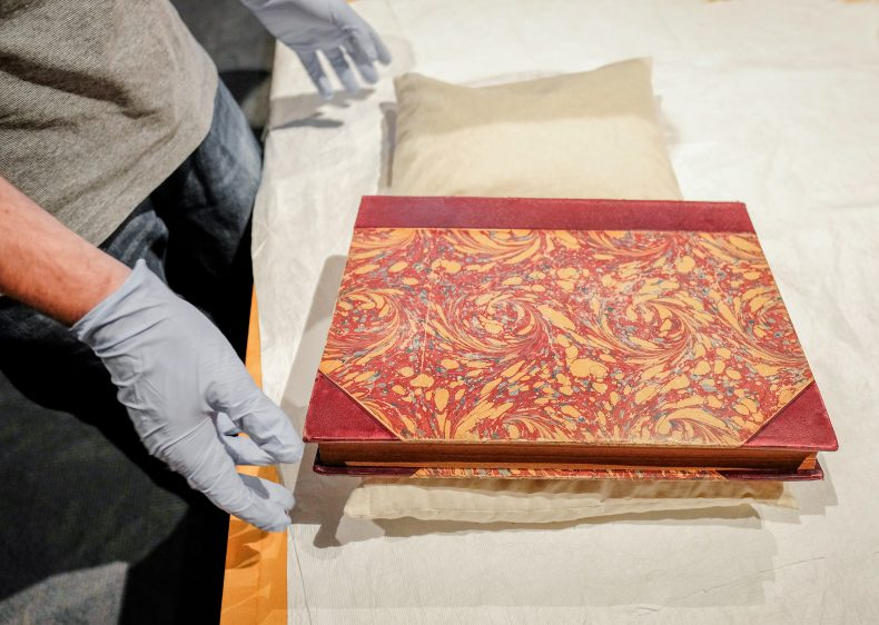 Martin shows one of the rare books in the collection with a marbled cover
