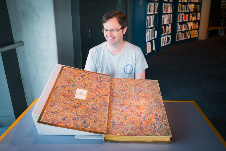 Martin sits with a large book with a very detailed marbled end-paper