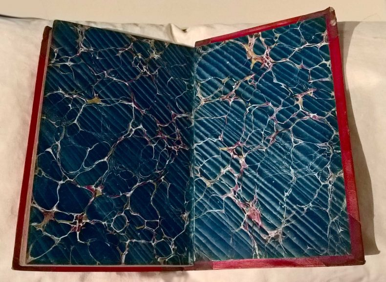 Red binded book with big dark blue marbling pattern on the inside cover