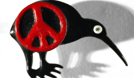Red CND symbol over a black kiwi enamel brooch