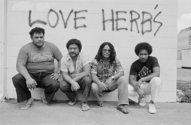 Photograph of the four members of Herbs crouching in front of a wall, which say Love Herbs painted on it