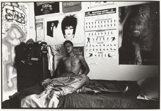 Photographic image of an unidentified young man with tattoos on his left arm - as seen in his bedroom, a number of posters adorn the back wall including one of Bob Marley
