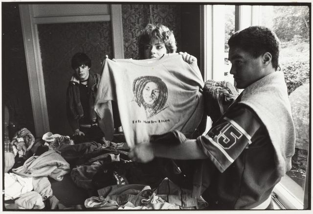 Photograph of a woman holding up a sweatshirt featuring Bob Marley's face