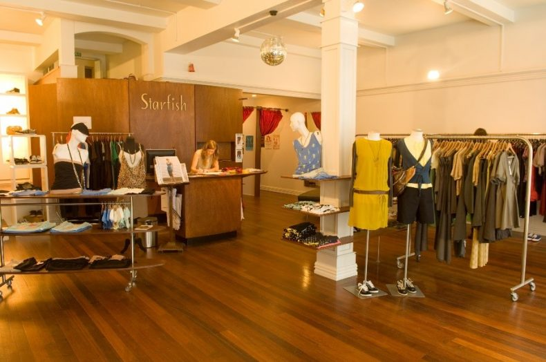 Photograph of the inside of Starfish's Wellington store, featuring a mid-century design and racks of clothing