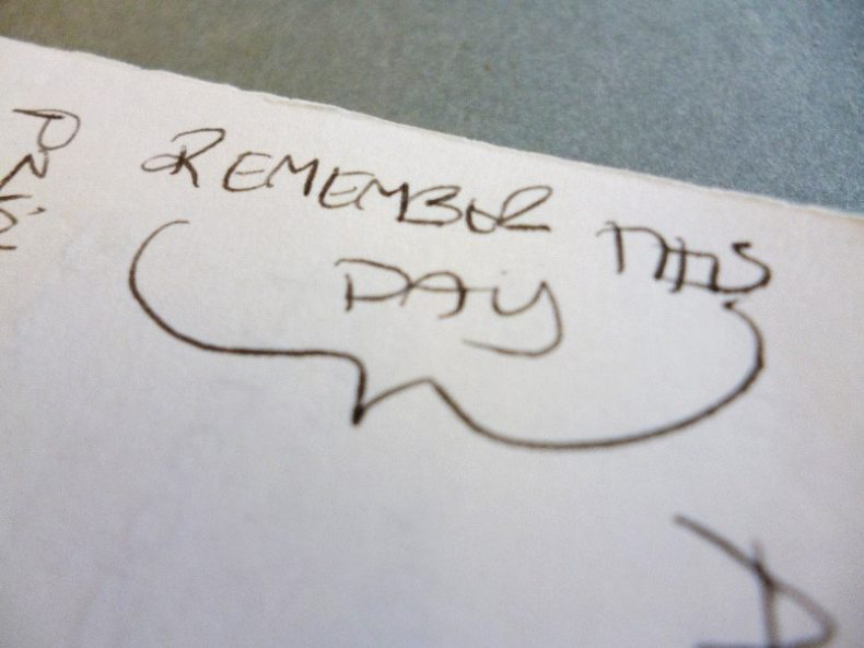 Close-up of a notebook with the words Remember this day written on it