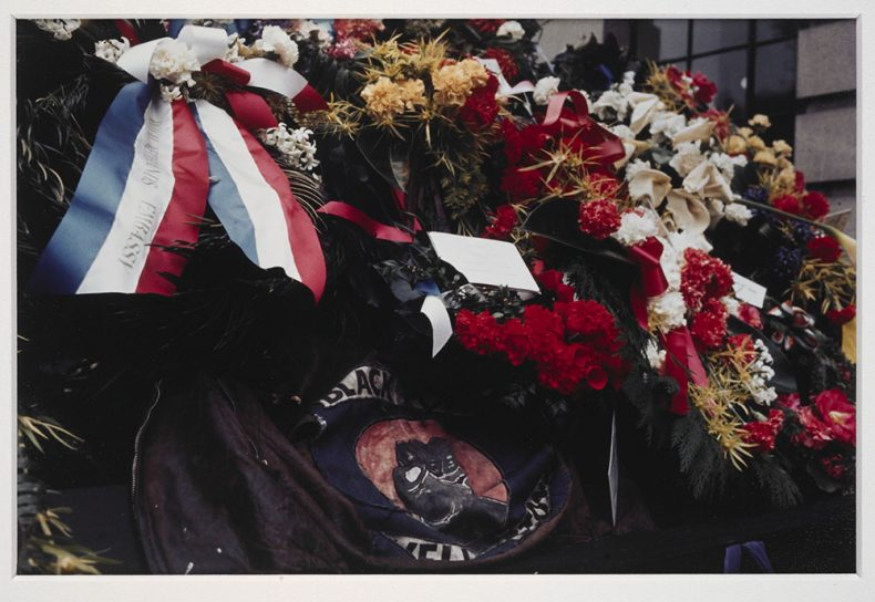 Wreaths lay on a coffin, as well as a Black Power jacket