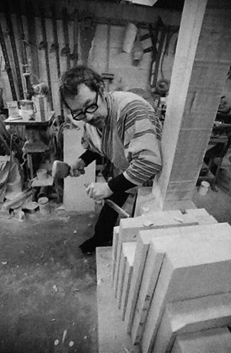 Black and white photograph of Guy Ngan working on a sculpture