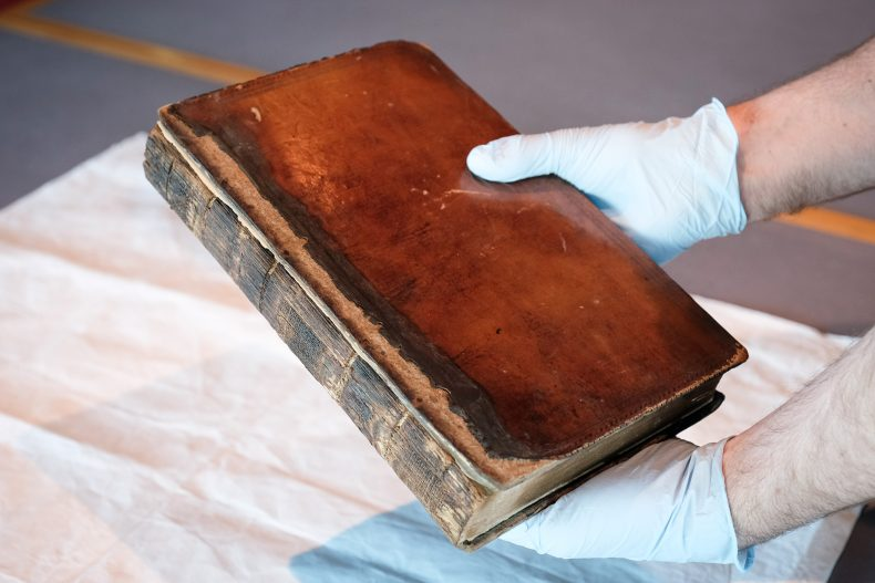 Martin holds a brown leather book with burnt edges