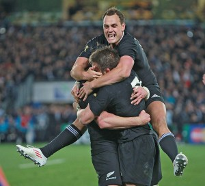 Rugby player Israel Dagg jumps onto teammates in celebration