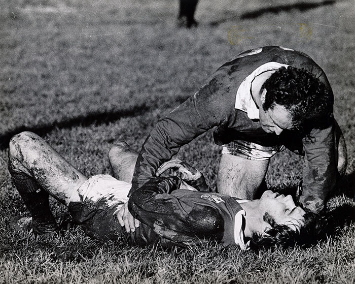 A man lies on the ground while another man offers help