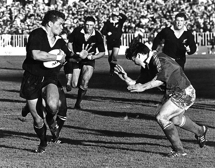 All Black Michael Jones runs with the ball past a French rugby player