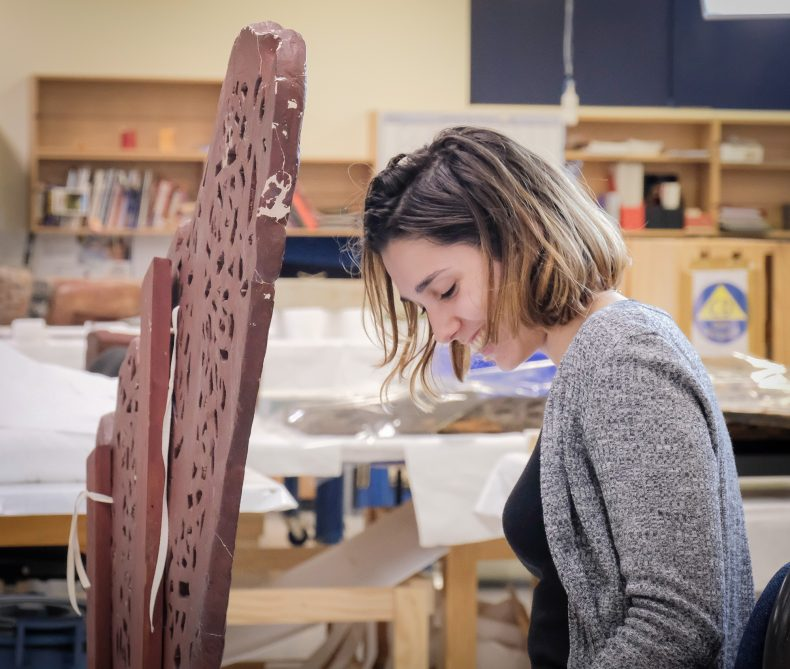 Charlotte smiling while restoring the canoe prow
