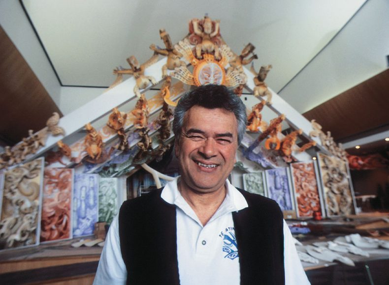Man stands in foreground with marae in the background
