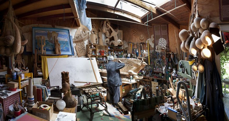 Man stands in his artist studio with art works and tools