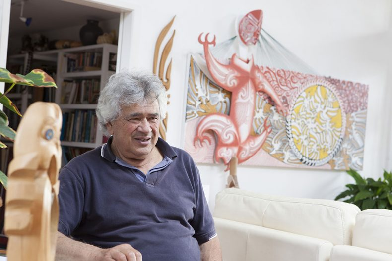 Man poses with an array of his art works on a wall