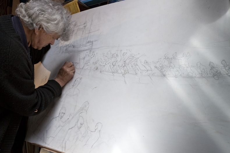 Man draws on a large sheet of paper