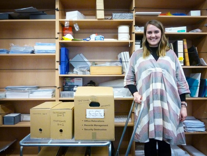 Ruby stands with some boxes in Te Papa's archives