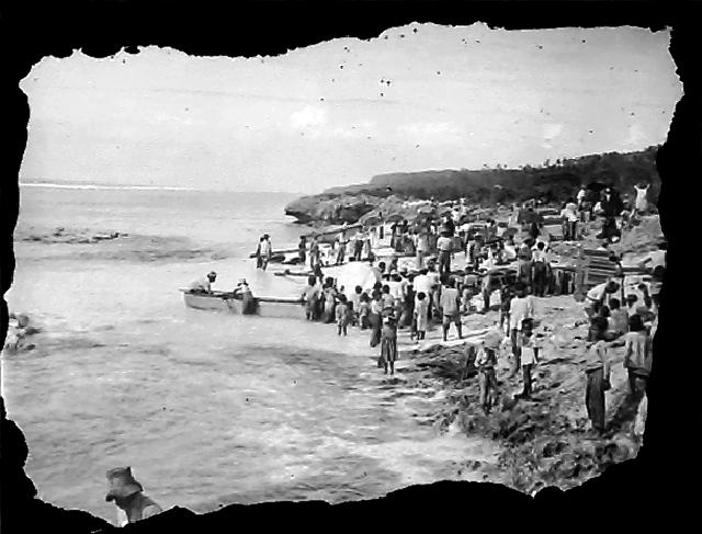 Photograph of people on a shoreline waiting for the arrival of supplies