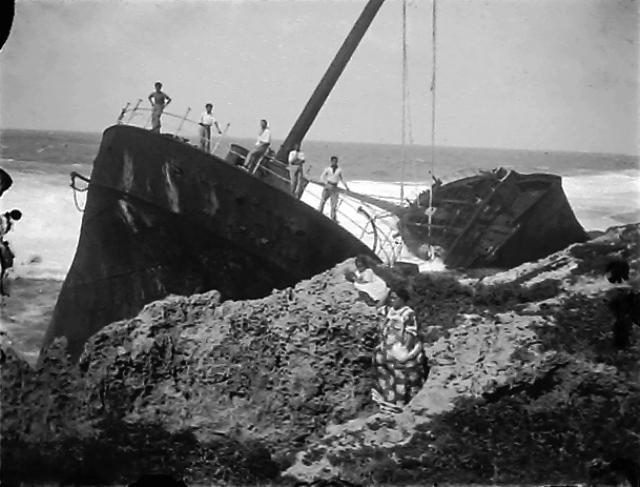 A ship, broken in two, against rocks with people standing on it