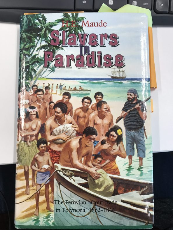 Front cover of the book Slavers in Paradise features a group of people behind a boat and a man putting a sack into the boat while another man stands guard with a gun