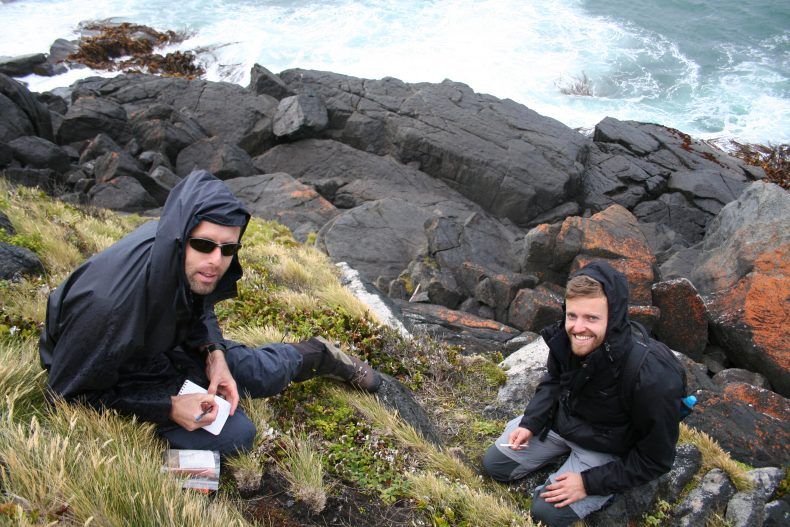 Two men on a grassy bank overlooking rocks and water