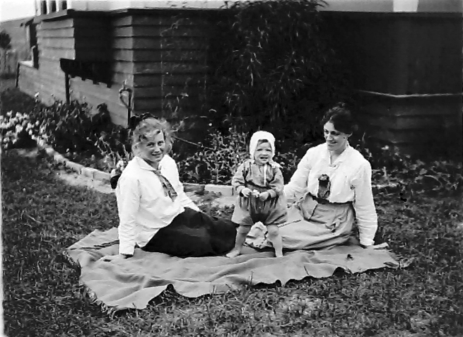 Two women and a baby sit on a picnic blanket