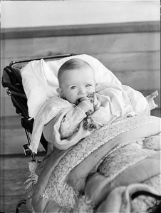 Close up of Nancy in pram with teething bone in mouth