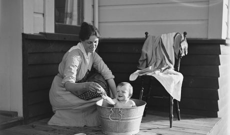 Woman bathes a baby in a bucket on a porch