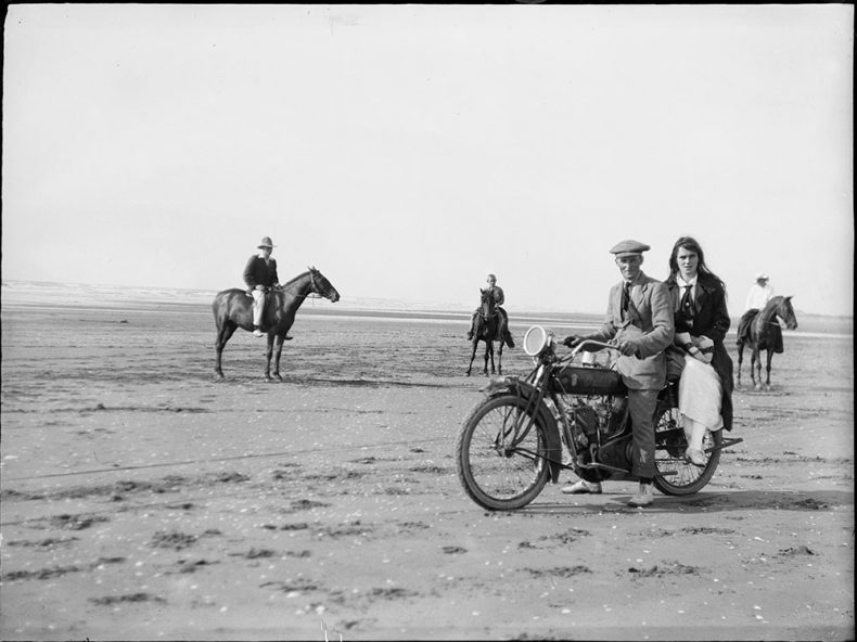 Two people sit on a motorcycle, and in the background three people sit on horseback